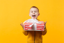 Little Kid Boy 3-4 Years Old Wearing Yellow Clothes Hold Gift Box Isolated On Orange Wall Background, Children Studio Portrait. People Sincere Emotions, Childhood Lifestyle Concept. Mock Up Copy Space