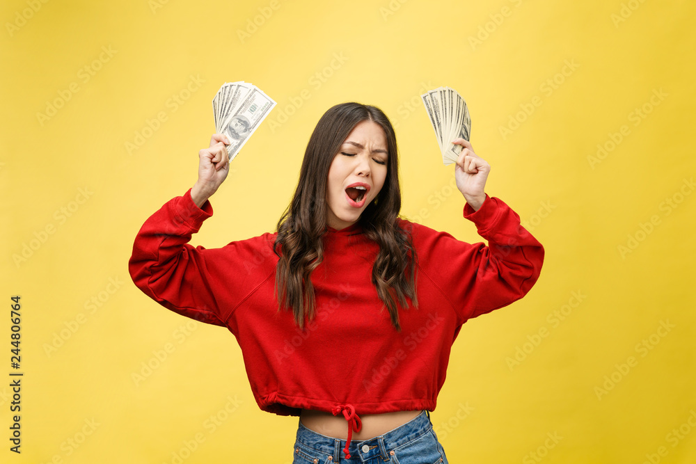 Fototapety, obrazy: Closeup of young beautiful woman with us dollar money in hand over yellow background, with copy space