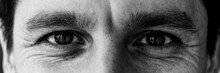 Male Eyes Of A Young Man To Compile An Identikit. Fragment Of The Wrinkled Face Of A Young Guy. Smiling Eyes Of A Man. Black And White Photo.