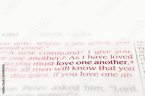 Bible text red letters reading love one another with copy