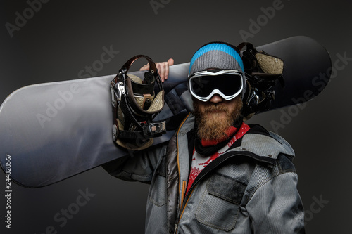 Brutal man with a red beard wearing a full equipment holding a snowboard on his shoulder, isolated on a dark background.