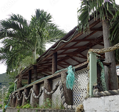 Fotografie, Obraz  A rustic open air hut with a tin roof, brown exposed beams, rough round wooden pillars, and white lattice walls draped with thick, twisted and braided ropes with palm trees under a white sky