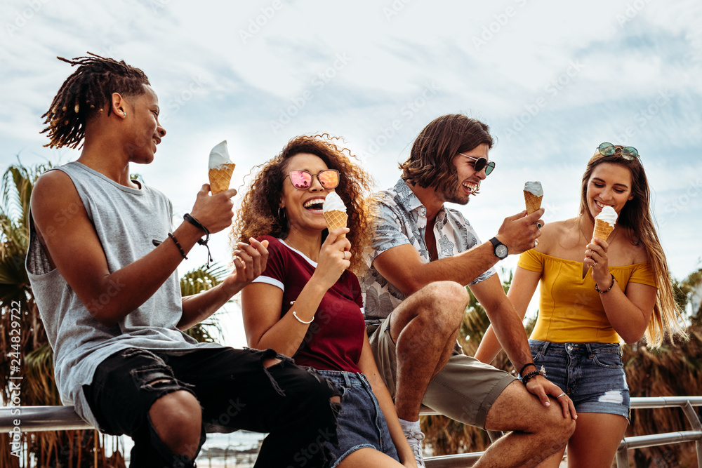 Fototapety, obrazy: Smiling young friends eating ice-cream outdoors