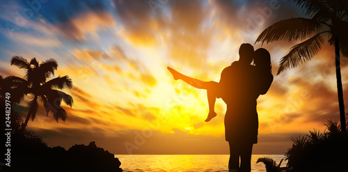 Fotografia  silhouette of a happy couple on tropical beach at sunset