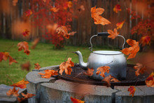 Autumn Scene Of Red Leaves Blowing Around A Kettle On The Grill Of A Fire Pit