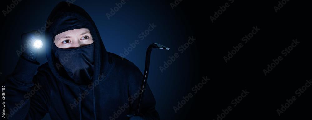 Fototapeta Maskierter Einbrecher in der Nacht mit Brecheisen und blau schwarzen Hintergrund