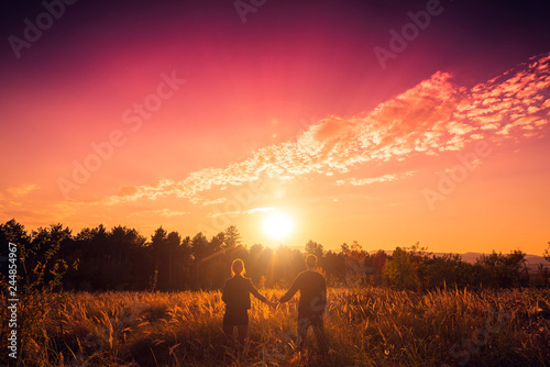 Fotografia  Couple in romantic sunset holding hands