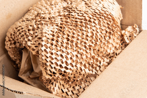 An open brown packaging box filled with recyclable brown filler paper.