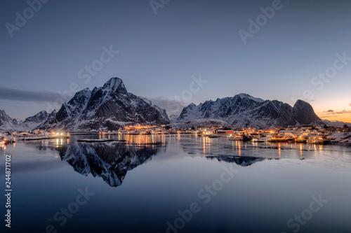 Foto auf Gartenposter Nordlicht Fishing village illumination with mountain range reflection on coastline at dawn