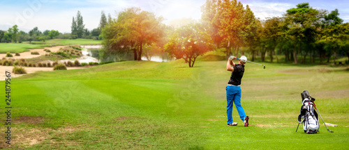 Panorama of Golfer hit sweeping golf ball on blurred  beautiful golf course with sunshine on background Fototapete