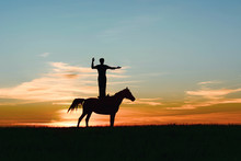 Silhouette Of Leader Inspired Man With Good Straight Posture, Standing On Horse And Showing Hand Gesture The Way, Direction, Copy Space, Pointing Index. Unusual Horseback Riding On Orange-blue Sunset