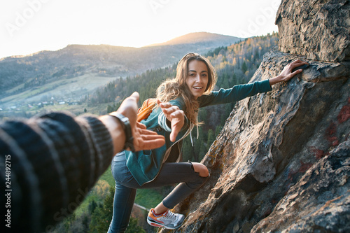 first person view of a young pretty woman hiker climbed on the cliff, looking co Fototapeta