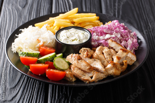 Doner kebab on a plate with french fries, salad and sauce close-up on a table. horizontal