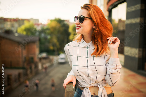 Fotografia  Attractive redhaired woman in sunglasses, wear on white blouse posing at street against modern building