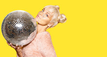 Portrait Of Blonde Model Wearing Festive Makeup And Posing With Glitter Ball On Yellow Background. Positivity And Disco Party Concept. Copy Space In Right Side