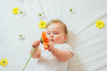Beautiful Baby Holding A Flower On White Blanket