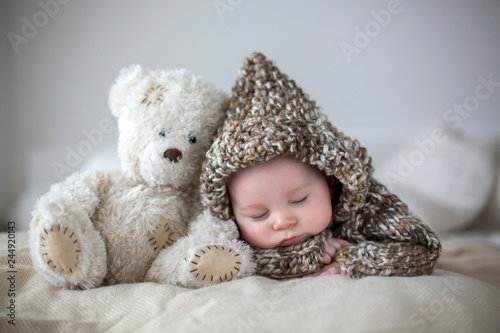 Fototapeta Little baby boy , sleeping at home with soft teddy bear toys obraz na płótnie