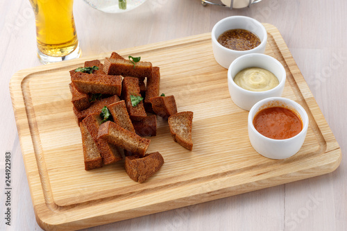 Fotografía  Croutons for beer with greens and sauce on a wooden board.