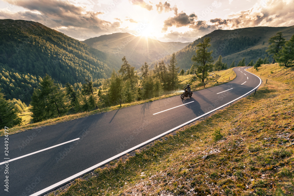 Fototapeta Motorcycle driver riding in Alpine road