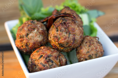 spicy mince pork balls with salad in a white plate on the table. Thai food (Larb Moo Tod)