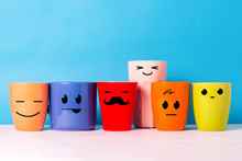A Lot Of Multi-colored Cups With Funny Faces On A Blue Background. The Concept Of A Friendly Company, A Big Family, Meeting Friends For A Cup Of Tea Or Coffee, Father's Day, Office, Boss Day.
