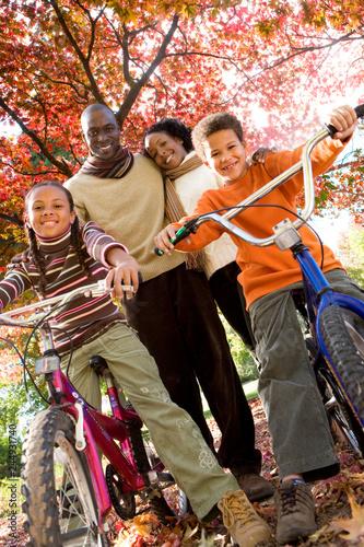 Portrait of smiling family riding bikes in autumn park