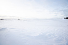 Panoramic View Of The Empty Snow-covered Country Field At Sunset. Evening Clouds. Norway