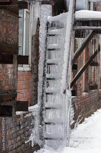 Fire escape covered with huge icicles, it is impossible to use the stairs/ great danger, сold winter, poor thermal insulation, ice stalactite, formation of icicles, frost and winter weather concept Wallpaper Mural