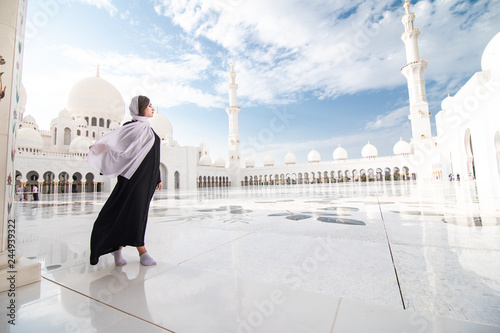Traditionally dressed arabic woman wearing black burka visiting Sheikh Zayed Grand Mosque in Abu Dhabi, United Arab Emirates.