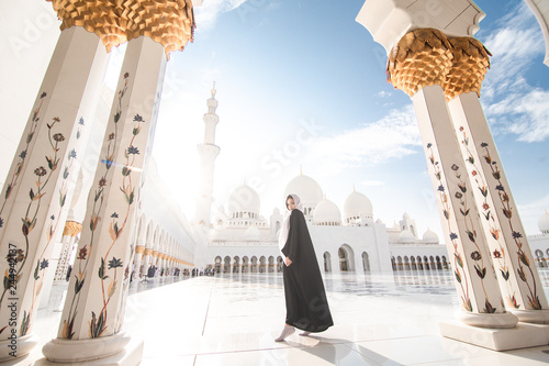 Cadres-photo bureau Abou Dabi Traveling by United Arabic Emirates. Young Woman in traditional abaya standing in the Sheikh Zayed Grand Mosque, famous Abu Dhabi sightseeing.