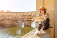 Happy Traveler Asian Women On A Vacation In Florence Admiring View At The Ponte Vecchio Famous Landmark During Trip In Italy, Europe
