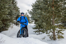 A Young Man Riding Fat Bicycle In The Winter