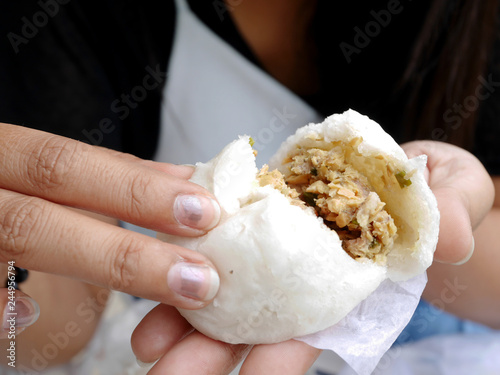 Thai women holding and show Kind of Chinese snacks steamed stuff buns before eat at outdoor of cafe and local restaurant
