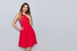 canvas print picture - Beautiful Woman In Red Dress Is Holding Hand On Chest And Smiling