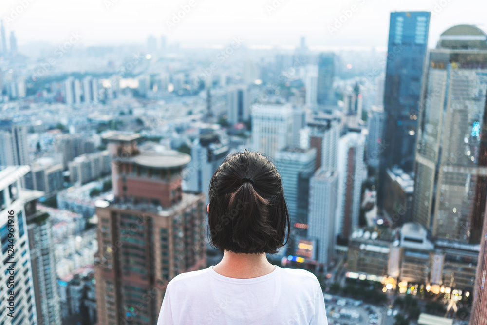 Fototapety, obrazy: Young woman looks out over the city at the top of the building