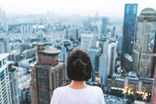 Young Woman Looks Out Over The City At The Top Of The Building