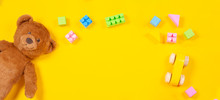 Baby Kids Toys Frame With Teddy Bear, Wooden Toy Car, Colorful Cubes On Yellow Background. Top View