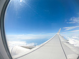 View from airplane window over airplane wing - Clouds and sky with sun reflection - aircraft, airship concept