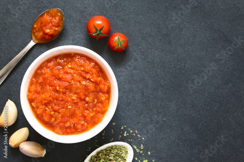 Homemade traditional Italian marinara or pomodoro tomato sauce made of fresh tomato, garlic, dried oregano and salt, photographed overhead on slate with natural light (Selective Focus on the sauce)