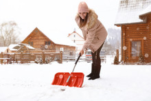 Young Woman Cleaning Snow With...