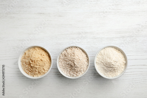 Bowls with different types of flour on white wooden background, top view. Space for text