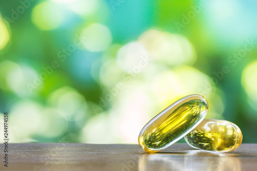 Fotografia  fish oil capsules on wooden table with natural background