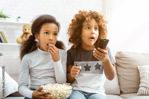 Fotografía  Little girls watching discovery channel and eating popcorn