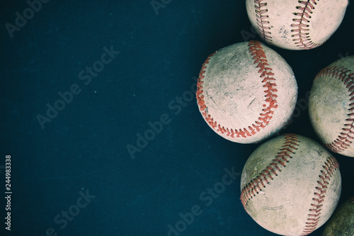 Old rugged group of baseballs on black background Wallpaper Mural