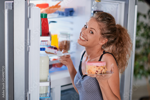 Woman taking cakes while standing in front of opened fridge.