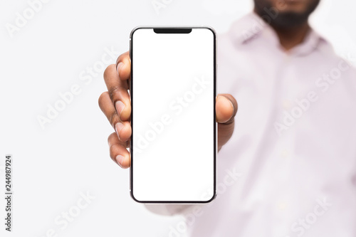 Fotografía  Businessman showing smart phone, with copy space