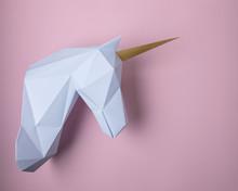 White 3d Papercraft Model Of Unicorn Head On Pink Background. Minimal Art Concept.