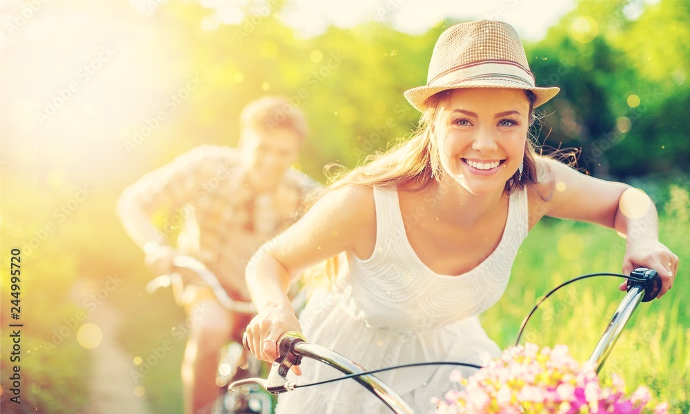 Fototapety, obrazy: Happy young couple cycling through the park