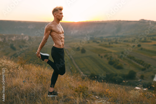 Handsome athlete warming up in countryside Wallpaper Mural