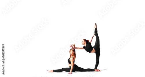 Two professional girls yoga trainer posing at studio  Side split and